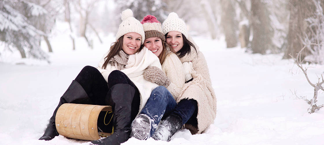 Three girls on sled in snow