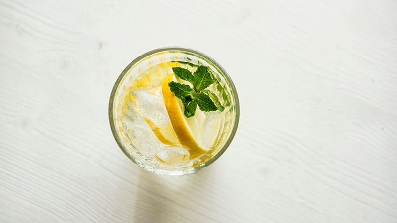 a glass of water with lemon and mint leaves