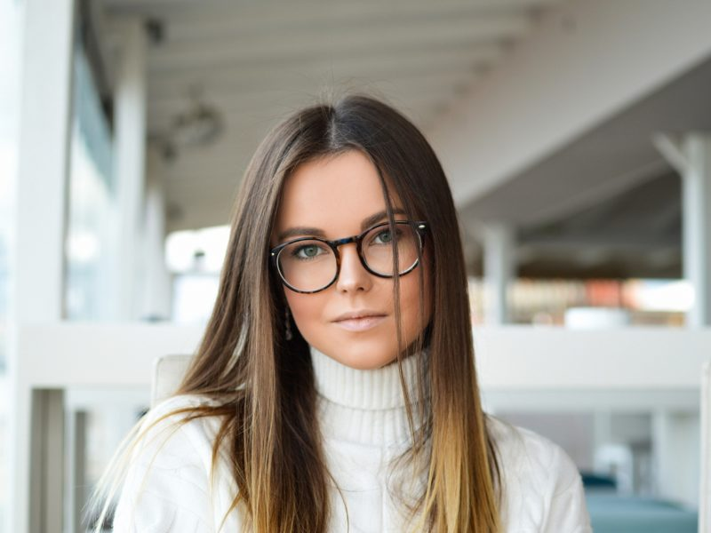 A young woman in white with eyeglasses
